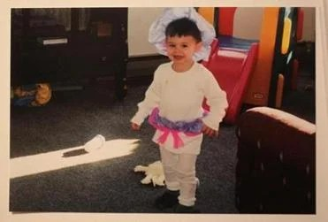 Wyatt, at age 3, wearing pink and purple.